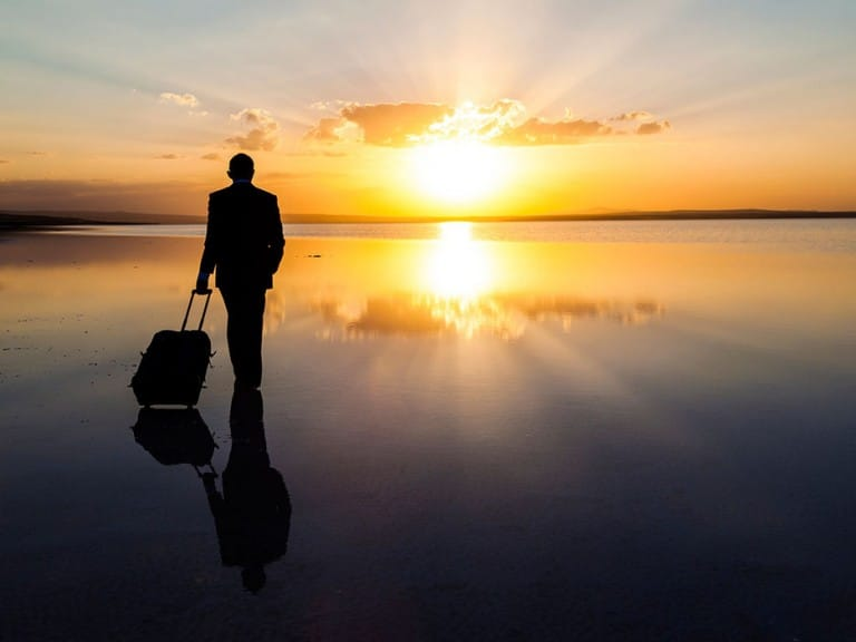 53e2f42ac2d3f39d3610bb62_man-beach-sunset-suitcase