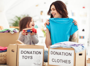 Mother and daughter preparing toys and clothes to donate for charity.